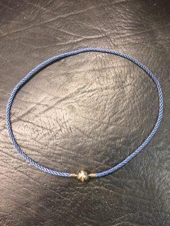 Jörg Heinz Stål smykkelås med guld bånd, samt blå silkesnor.